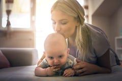 在床上的愉快的母亲与她的小男婴在家 免版税库存照片