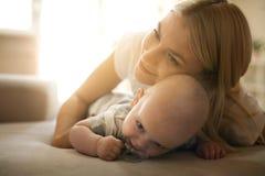 在床上的愉快的母亲与她的小男婴在家 免版税库存图片