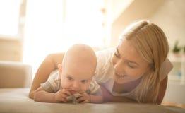 在床上的愉快的母亲与她的男婴 图库摄影