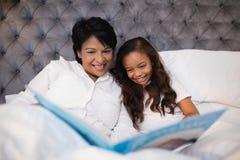 在床上的愉快的祖母和孙女阅读书 库存图片