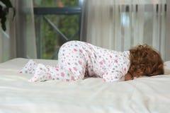 在床上的愉快的红发婴孩 免版税库存图片