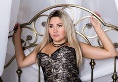 在床上的束腰和牛仔布的白肤金发的妇女在明亮的屋子里 免版税图库摄影