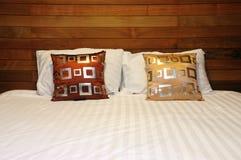 在床上的枕头在木卧室 免版税图库摄影