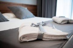 在床上的浴巾在旅馆客房 免版税库存图片