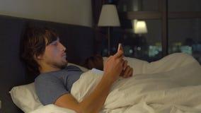 在床上的男人和妇女,有智能手机的人,当妇女睡觉时 在婚姻的问题和男女两性之间 股票录像
