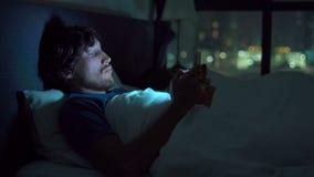 在床上的男人和妇女,有智能手机的人,当妇女睡觉时 在婚姻的问题和男女两性之间 影视素材