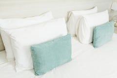 在床上的白色和绿色枕头 免版税库存图片