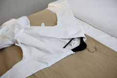 在床上的白色外套 库存图片