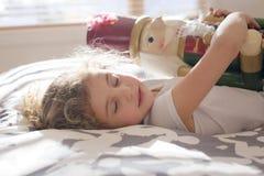 在床上的秀丽孩子拿着一个胡桃钳 图库摄影
