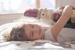 在床上的秀丽孩子拿着一个胡桃钳 库存照片