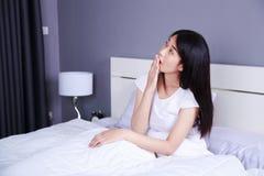 在床上的美丽的妇女在卧室 图库摄影