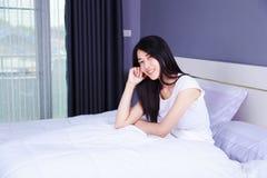 在床上的美丽的妇女在卧室 免版税库存图片