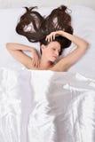 在床上的美丽的妇女在白色亚麻布下 免版税库存图片