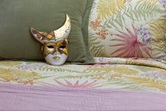 在床上的被绘的面具 库存照片