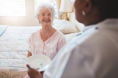 在床上的资深妇女与给疗程的护士 免版税库存照片