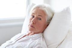 在床上的资深妇女患者在医院病房 免版税库存图片