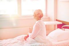 在床上的资深妇女患者在医院病房 免版税库存照片