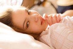 在床上的迷人的女孩在被弄脏的早晨 免版税库存照片