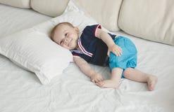 在床上的逗人喜爱的微笑的男婴的被定调子的图象 库存照片