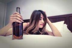在床上的醉酒的妇女与瓶 免版税库存图片