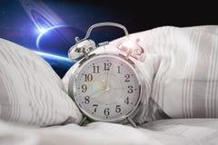 在床上的闹钟在外层空间 库存照片