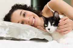 在床上的黑人妇女画象宠爱她可爱的猫 爱,关心,宁静的概念对动物的 免版税库存照片