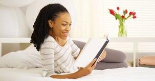 在床上的黑人妇女读书 免版税库存图片