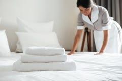 在床上的年轻旅馆佣人安装枕头 图库摄影