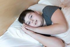 在床上的13年的少年 免版税库存照片