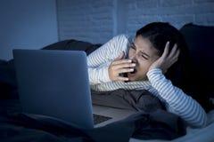 在床上的年轻美丽的西班牙互联网上瘾者妇女与计算机疲倦的膝上型计算机打呵欠 库存照片