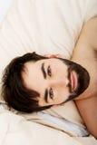 在床上的年轻肌肉人 免版税库存照片