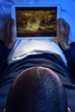 在床上观看一部电影或一个系列在他的片剂的年轻人 库存图片