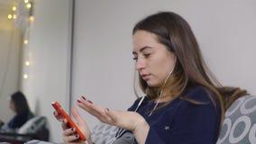 在床上跳舞听到在耳机的音乐的一个少妇在一个手机 股票录像