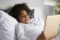 在床使用数字式片剂,关闭的微笑的女孩谎言  免版税库存照片