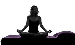 在床剪影的女子瑜伽坐的莲花姿势 图库摄影