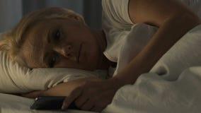 在床和观看的家庭照片上的孤独的成熟妇女在手机,失眠 股票视频