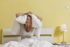 在床和结束上的女性开会她的有枕头的耳朵 库存照片