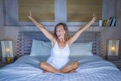 在床在家卧室听音乐与耳机和机动性的互联网歌曲的可爱和愉快的30s白种人白肤金发的妇女 图库摄影