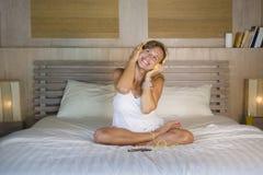 在床在家卧室听音乐与耳机和机动性的互联网歌曲的可爱和愉快的30s白种人白肤金发的妇女 免版税库存照片