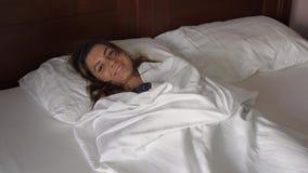 在床在盖子下,拉扯毯子上的深色的妇女有乐趣微笑 影视素材