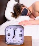 在床头柜人困不剃须的有胡子的面孔睡眠的闹钟在眼罩背景中 健康睡眠技巧 被宣扬的 库存照片
