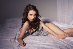 在床家的美丽的深色的妇女画象 免版税图库摄影