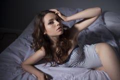 在床家的美丽的深色的妇女画象 库存照片