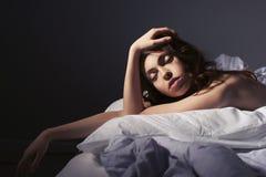 在床家的美丽的深色的妇女画象 免版税库存照片