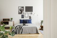 在床旁边的白色木洗脸台与深蓝枕头、灰色鸭绒垫子和镶边的黑白毯子在卧室 免版税库存照片