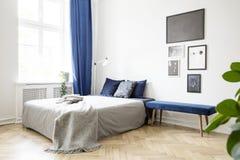 在床旁边的长凳与在明亮的卧室内部的灰色毯子与海报和蓝色装饰 实际照片 库存照片