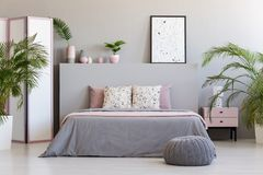 在床灰色床头板的被仿造的海报与枕头的在bedroo 图库摄影