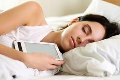 在床睡觉的年轻美丽的深色的妇女画象 库存照片