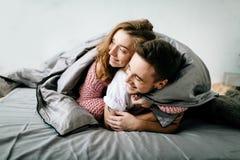 在床罩下的快乐的夫妇在他们的床上 附庸风雅 在女孩的软的焦点 图库摄影
