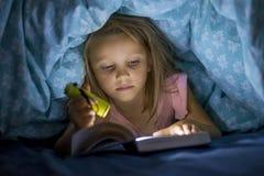 在床罩阅读书下的美好的美好和相当小的白肤金发的女孩6到8岁在黑暗在与火炬光的晚上 免版税图库摄影